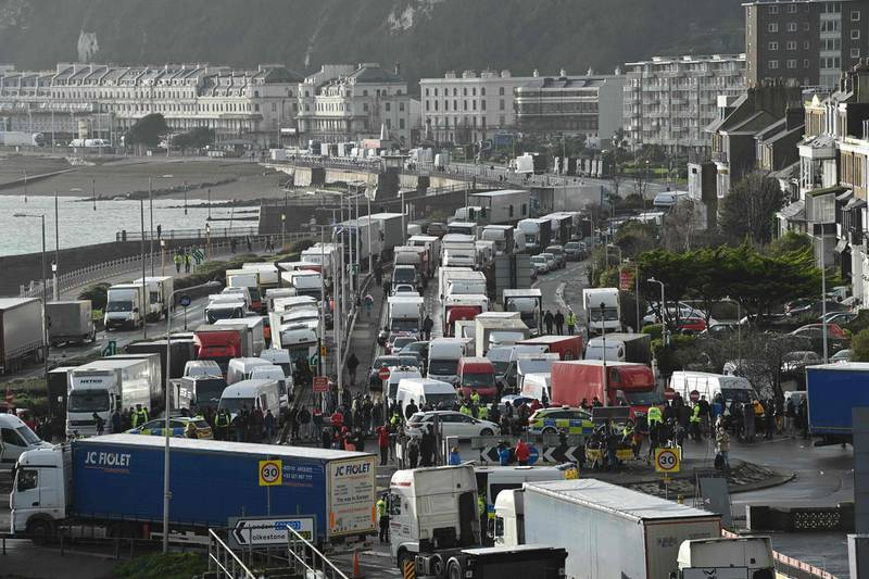 Drivers stand with their HGV freight lorries blocking the entrance trying to enter the port of Dover in Kent, south east England, on December 23, 2020, that is still cordoned after the UK and France agreed a protocol to reopen the border to accompanied freight arriving in France from the UK requiring all lorry drivers to show a negative Covid-19 test.  France and Britain reopened cross-Channel travel on Wednesday after a 48-hour ban to curb the spread of a new coronavirus variant but London has warned it could take days for thousands of trucks blocked around the port of Dover to get moving.  / AFP / JUSTIN TALLIS