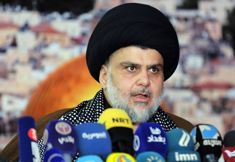 """Iraq's powerful Shiite cleric Moqtada al-Sadr addresses the media with a giant photo of Jerusalem's Dome of the Rock mosque in the background in the shrine city of Najaf in central Iraq on December 7, 2017 to denounce US President Donald Trump's decision to recognise Jerusalem as Israel's capital.  Sadr, who heads his own militia, demanded the closure of the American embassy in Baghdad and warned that """"we can reach Israel through Syria"""". / AFP PHOTO / Haidar HAMDANI"""