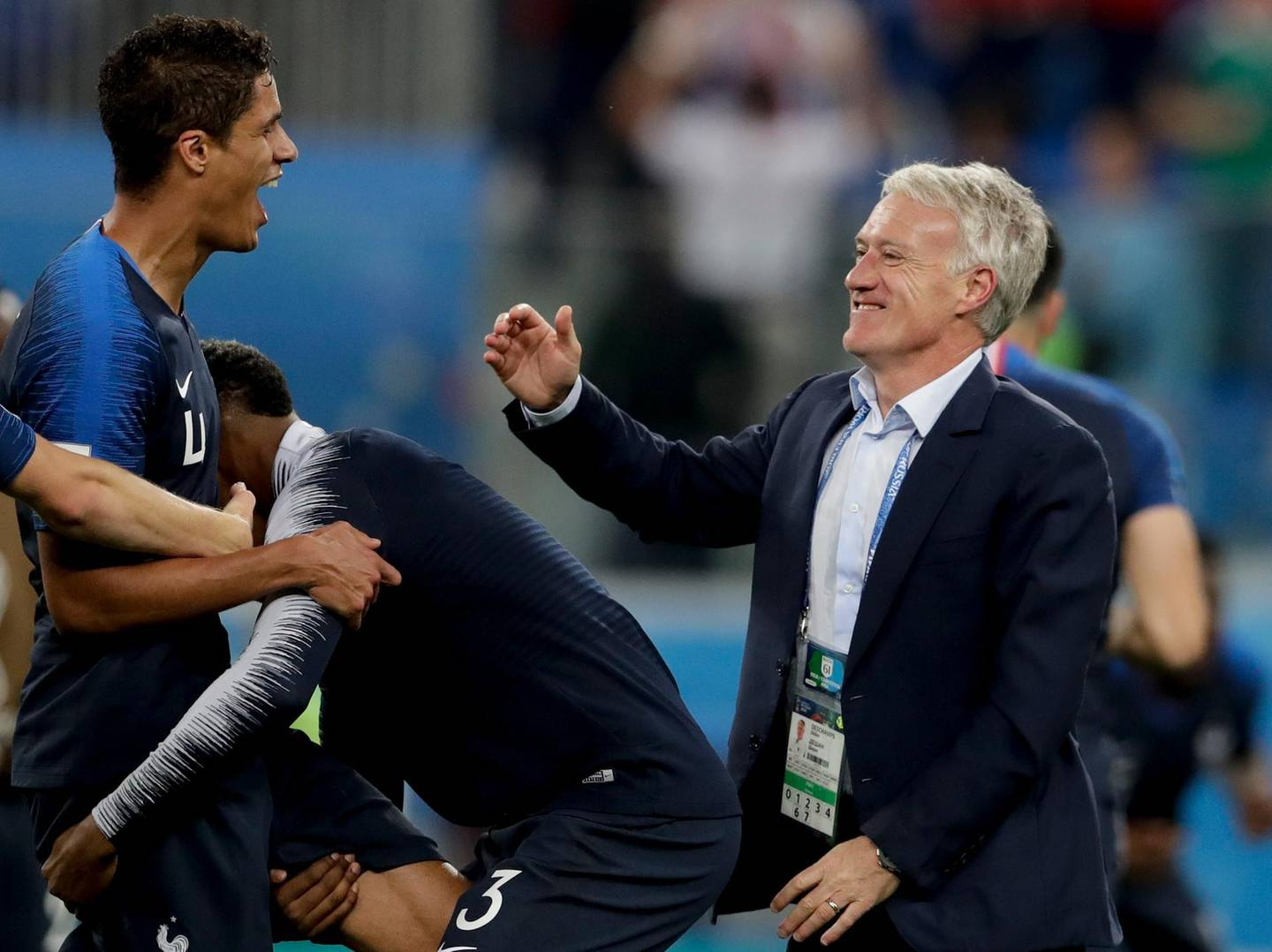 France head coach Didier Deschamps, right, and Raphael Varane celebrate at the end of the semifinal match between France and Belgium at the 2018 soccer World Cup in the St. Petersburg Stadium, in St. Petersburg, Russia, Tuesday, July 10, 2018. France won 1-0. (AP Photo/Petr David Josek)