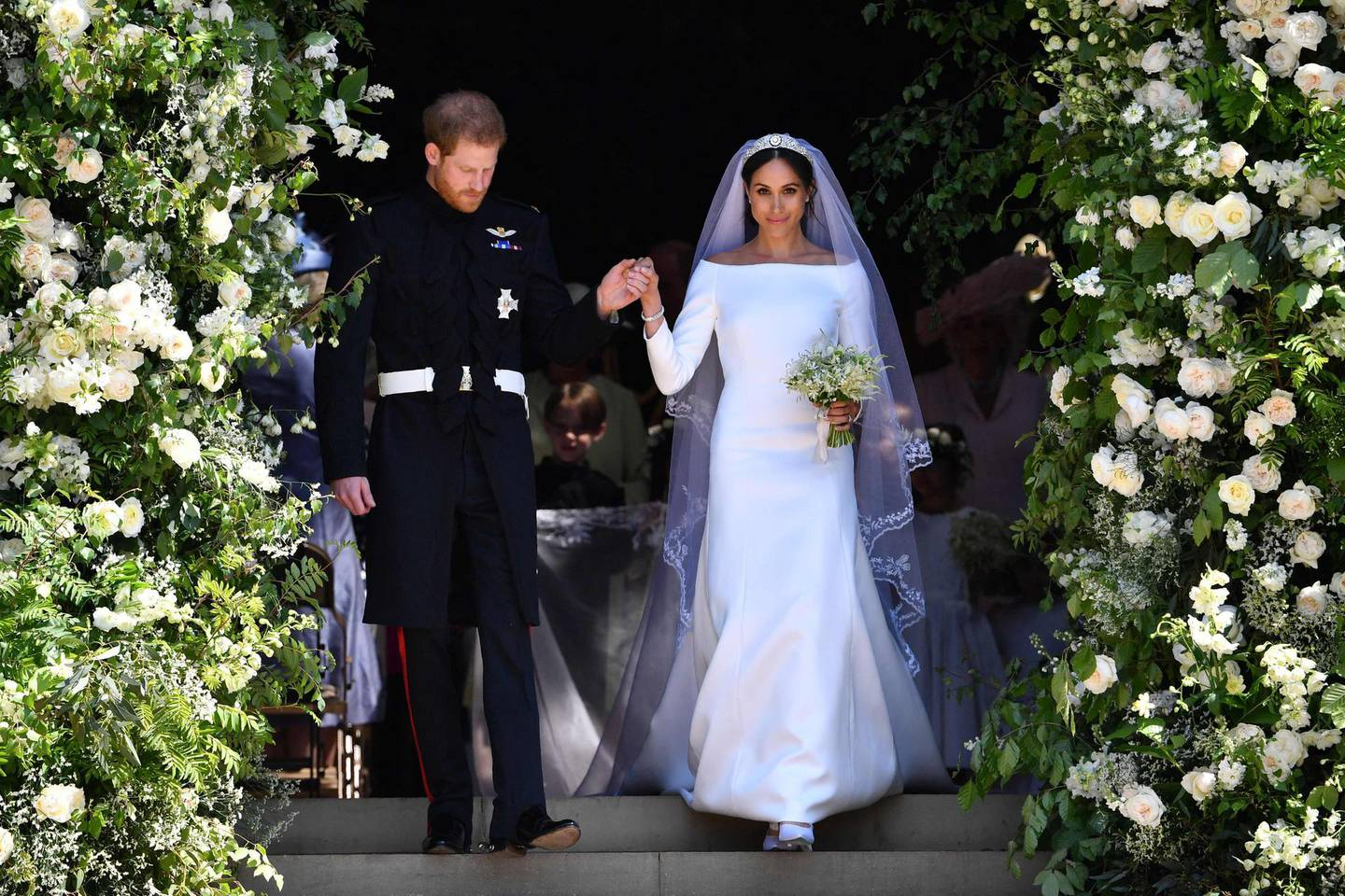 (FILES) In this file photo taken on May 19, 2018 Britain's Prince Harry, Duke of Sussex and his wife Meghan, Duchess of Sussex walk down the west steps of St George's Chapel, Windsor Castle, in Windsor, after their wedding ceremony. Meghan Markle has experienced remarkable highs and lows during a tumultuous period in which she married into royalty and became a mother before souring on life in Britain and returning to the United States. The 39-year-old American former television actress shot to global stardom with her engagement to Prince Harry in 2017 and their fairytale wedding six months later. She gave birth to their son, Archie, in 2019.  / AFP / POOL / Ben STANSALL