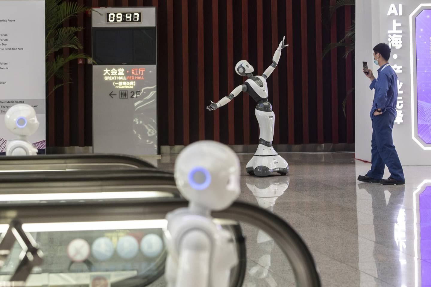 A member of the event staff takes a photograph of a humanoid robot in the exhibition display area at the World AI Conference in Shanghai, China, on Thursday, July 9, 2020. China will invest an estimated $1.4 trillion over six years to 2025, calling on urban governments and private tech giantsto lay fifth generation wireless networks, install cameras and sensors, and develop AI software that will underpin autonomous driving to automated factories and mass surveillance, according to the National People's Congress Work Report released in May. Photographer: Qilai Shen/Bloomberg