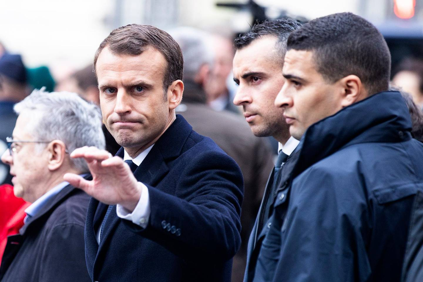 epa07205324 French President Emmanuel Macron (C) waves to citizens as he assesses the damages of the 'Yellow Vests' protest a day earlier, next to the Champs Elysee in Paris, France, 02 December 2018 (03 December 2018). The so-called 'gilets jaunes' (yellow vests) are a protest movement, which reportedly has no political affiliation, is protesting across the nation over high fuel prices.  EPA/ETIENNE LAURENT