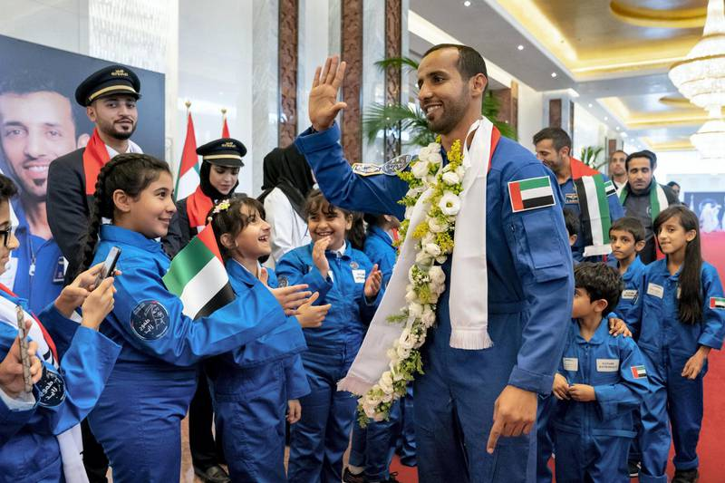 ABU DHABI, UNITED ARAB EMIRATES - October 12, 2019: Hazza Ali Al Mansoori, the first UAE Astronaut to be deployed on a space mission to the International Space Station (ISS) (C) and Sultan Saif Al Neyadi, a member of the International Space Station (ISS) mission back-up team (back), greet school children during a homecoming reception at the Presidential Airport.  ( Hamad Al Mansoori for the Ministry of Presidential Affairs ) ---