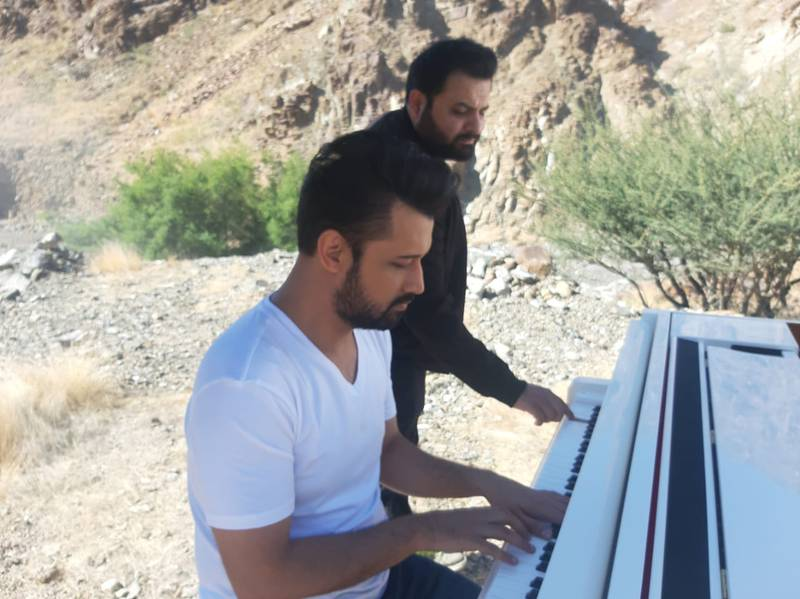 Two men playing a piano outdoors