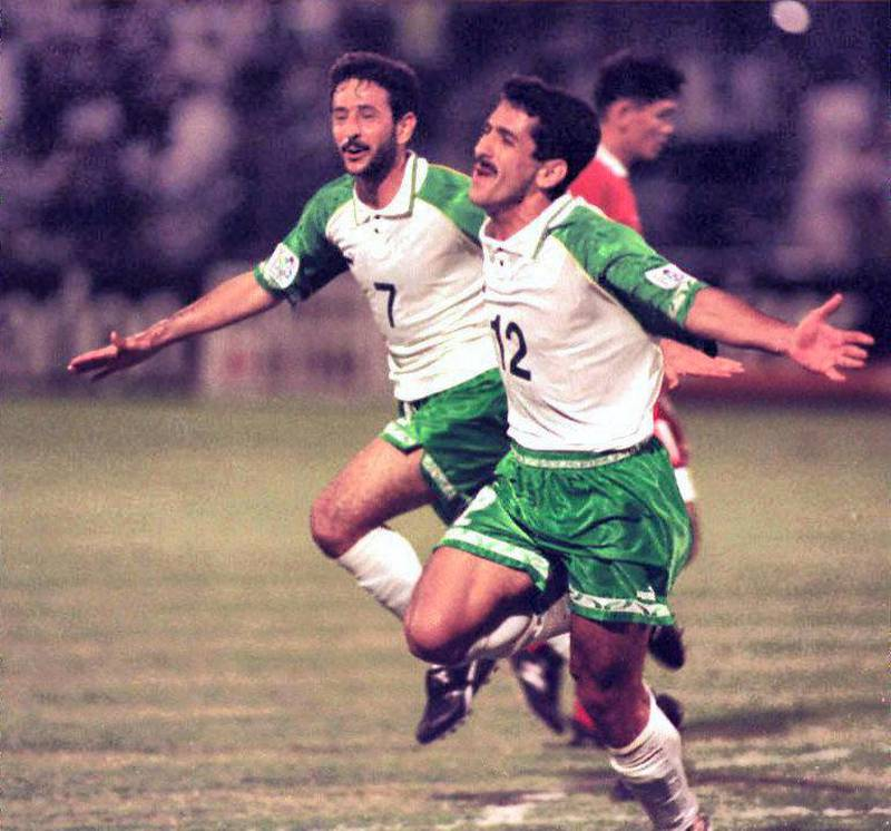 Iraqi forwards Haydar Majed (R) and Khalid Sabbar (L) jubilate 11 December after their victory against Thailand in an Asian Cup match in Dubai. Iraq defeated Thailand 4-1 and qualified for the quarter-finals against arch enemy Iran. (Photo by RAMZI HAIDAR / AFP)