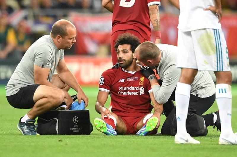 KIEV, UKRAINE - MAY 26:  Mohamed Salah of Liverpool receives treatment from the medical team during the UEFA Champions League Final between Real Madrid and Liverpool at NSC Olimpiyskiy Stadium on May 26, 2018 in Kiev, Ukraine.  (Photo by Michael Regan/Getty Images)