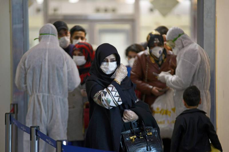 TOPSHOT - Medical staff in protective gears distribute information sheets to Iraqi passengers returning from Iran at Najaf International Airport on March 5, 2020. Iraqi health authorities announced the country's first two deaths from the new coronavirus, one in the capital Baghdad and the other in the autonomous Kurdish region. / AFP / Haidar HAMDANI
