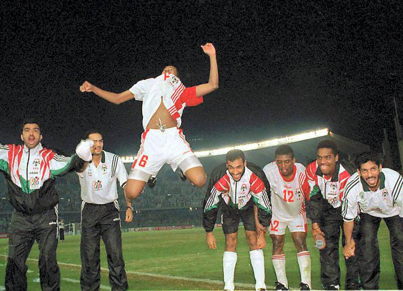 """United Arab Emirates's Ismail Ismail leaps up in the air as he celebrates with his team their victory over Iraq after their Asian Cup first quarter final 15 December Abu Dhabi. The UAE beat Iraq 1-0  with a """"sudden death"""" goal from a 35 yards free kick by Abdel Hussain in the 14th minute of extra time. (Photo by JORGE FERRARI / AFP)"""