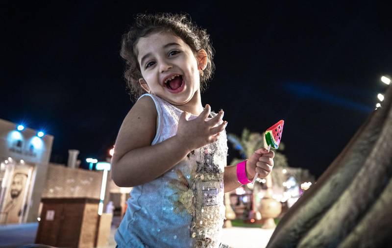 Abu Dhabi, United Arab Emirates, November 23, 2020.   Sheikh Zayed Heritage Festival celebrations at Al Wathba.  Karolina Ahmed, 3, enjoys her watermelon lolipop while on a horse ride.Victor Besa/The NationalReporter:  Samia BadihSection:  NAFor:  Standalone/Stock