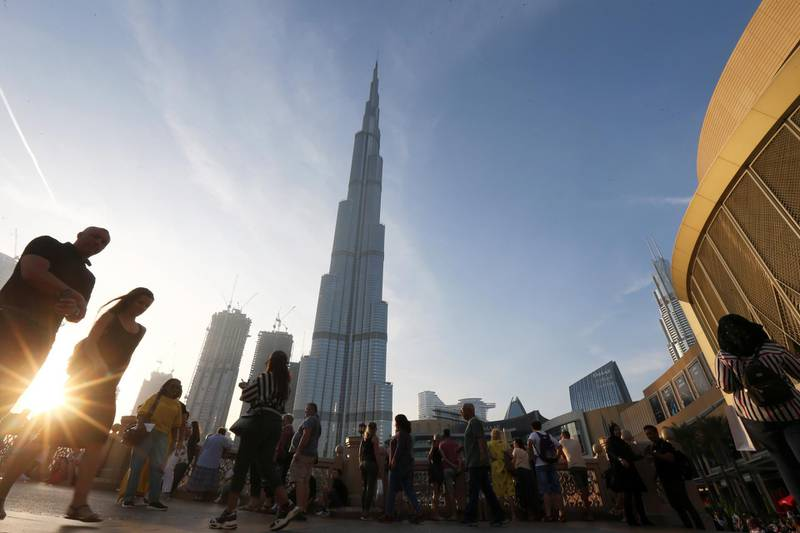 People are seen in front of Burj Khalifa, the world tallest building, in Dubai, United Arab Emirates March 12, 2020. Picture taken March 12, 2020. REUTERS/Satish Kumar