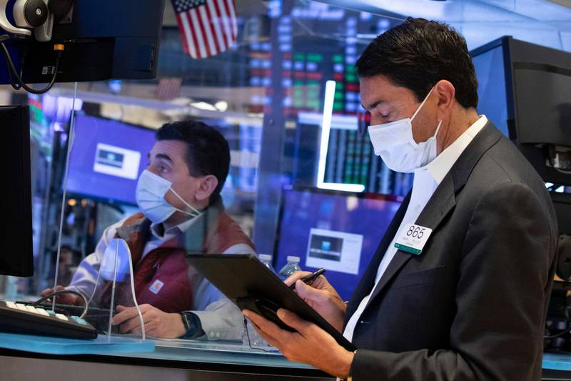 In this photo provided by the New York Stock Exchange, trader Mark Muller, right, and specialist Peter Mazza work on the trading floor, Wednesday, March 24, 2021. Stocks were moving mostly higher on Wednesday, helped by a recovery of bank and industrial stocks. Bond yields were steady after rising earlier this week. (Nicole Pereira/New York Stock Exchange via AP)