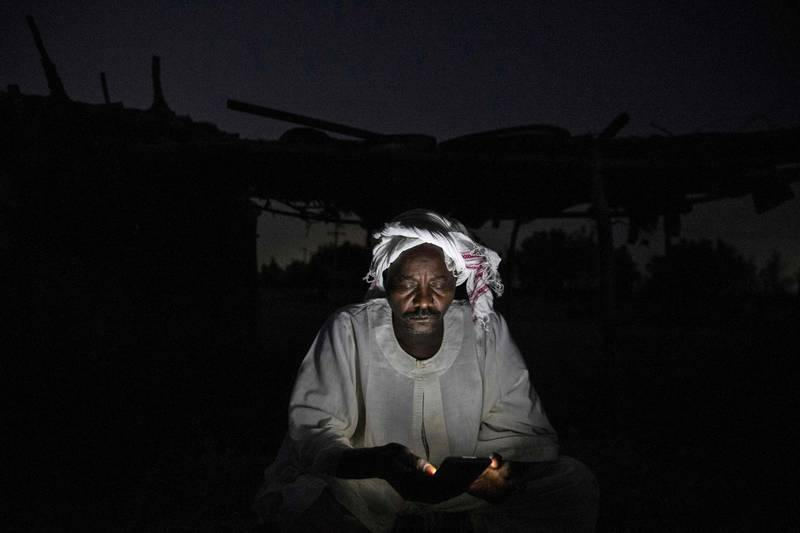 A Sudanese man checks his phone as he sits in darkness at al-Ikhlas village in the west of the city of Omdurman, on March 18, 2021.  / AFP / ABDULMONAM EASSA