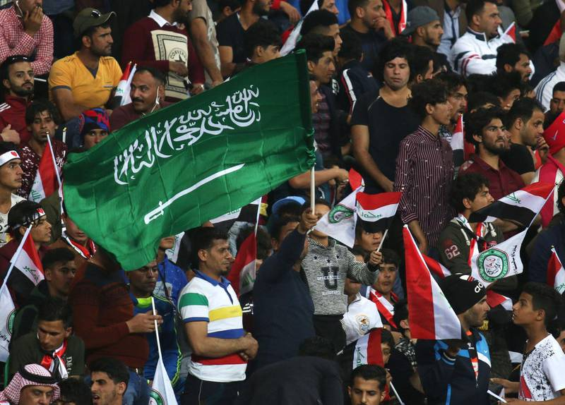 A football fan waves a Saudi Arabian flag during the friendly football match between Iraq and Saudi Arabia at the Basra Sports city stadium in Basra on February 28, 2018.  Iraq has not played full internationals on home turf ever since its 1990 invasion of Kuwait that sparked an international embargo. Iraq won the match 4-1 / AFP PHOTO / HAIDAR MOHAMMED ALI