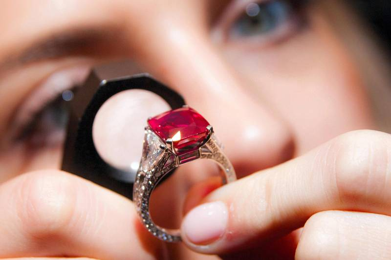 E95CKT Sotheby's, London, UK. 20th October, 2014. Jewels from the famed collection of Dimitri Mavrommatis will be offered in Sotheby's Geneva sale of Magnificent Jewels & Noble Jewels on 12 November. PICTURED: A woman examines the 8.62 carat cushion-shaped Burmese Ruby, known as the Graff Ruby, a truly exceptional example of Mogok rubies, which are  arguably the rarest of all gemstones, with the ring having an estimated value of £4.2 - 5million. Credit:  Paul Davey/Alamy Live News