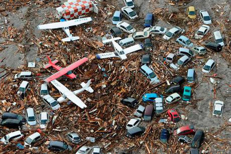 Cars and airplanes swept by a tsunami are pictured among debris at Sendai Airport, northeastern Japan March 11, 2011. A massive 8.9 magnitude quake hit northeast Japan on Friday, causing many injuries, fires and a ten-metre (33-ft) tsunami along parts of the country's coastline. There were several strong aftershocks and a warning of a 10-metre tsunami following the quake, which also caused buildings to shake violently in the capital Tokyo. A tsunami warning has been issued for the entire Pacific basin except for the mainland United States and Canada following a huge earthquake that hit Japan on Friday, the Pacific Tsunami Warning Center said.  REUTERS/KYODO (JAPAN - Tags: DISASTER TRANSPORT) FOR EDITORIAL USE ONLY. NOT FOR SALE FOR MARKETING OR ADVERTISING CAMPAIGNS. JAPAN OUT. NO COMMERCIAL OR EDITORIAL SALES IN JAPAN. YES *** Local Caption ***  SIN23_JAPAN-QUAKE-_0311_11.JPG
