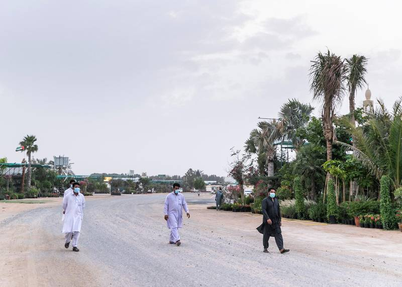 DUBAI, UNITED ARAB EMIRATES. 13 APRIL 2020. Three men in face mask walking iby nurseries in Warsan.(Photo: Reem Mohammed/The National)Reporter:Section: