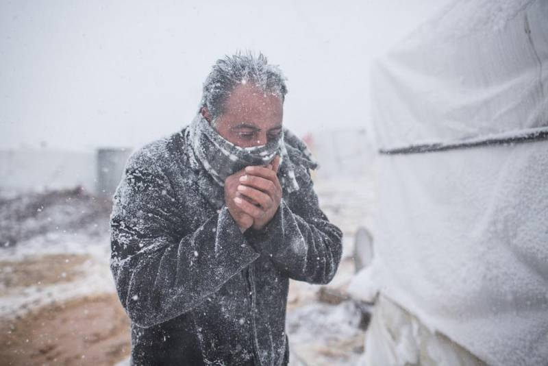 Lebanon / Syrian Refugees / A Syrian man tries to warm himself as snow falls in the Terbol tented settlement in the Bekaa Valley, on 11 December 2013. The Alexa storm has brought severe weather to Lebanon and much of the Middle East, affecting tens of thousands of Syrian refugees. / UNHCR / A. McConnell / December 2013