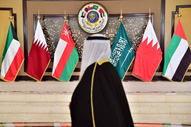 A man walks past the flags of the countries attending the Gulf Cooperation Council (GCC) summit at Bayan palace in Kuwait City on December 5, 2017. The Gulf Cooperation Council, which launches its annual summit today in Kuwait amid its deepest ever internal crisis, comprises six Arab monarchies who sit on a third of the world's oil. A political and economic union, the GCC comprises Saudi Arabia, the United Arab Emirates, Kuwait, Qatar, Oman and Bahrain. Dominated by Riyadh, it is a major regional counterweight to rival Iran.  / AFP PHOTO / GIUSEPPE CACACE
