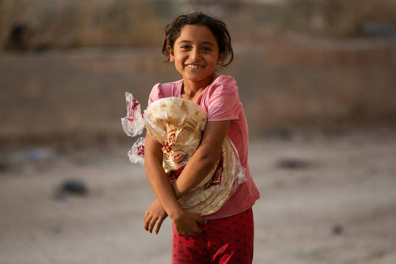 """A Syrian girl, displaced due to the ongoing Turkish military operation in northeastern Syria, receives bread from a Turkish NGO in the town of Ayn al-Arus, south of the border town of Tal Abyad on October 18, 2019. - Turkey had agreed to suspend its Syria offensive for five days but President Recep Tayyip Erdogan warned on Friday he would resume a full-scale operation against Kurdish forces if they do not withdraw from a border """"safe zone."""" (Photo by Bakr ALKASEM / AFP)"""