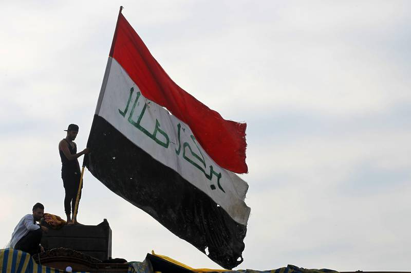 TOPSHOT - An Iraqi demonstrator waves a large national flag in the capital Baghdad's Tahrir Square, amid ongoing anti-government protests, on December 6, 2019.  Tahrir has become a melting pot of Iraqi society, occupied day and night by thousands of demonstrators angry with the political system in place since the aftermath of the US-led invasion of 2003 and Iran's role in propping it up. / AFP / AHMAD AL-RUBAYE