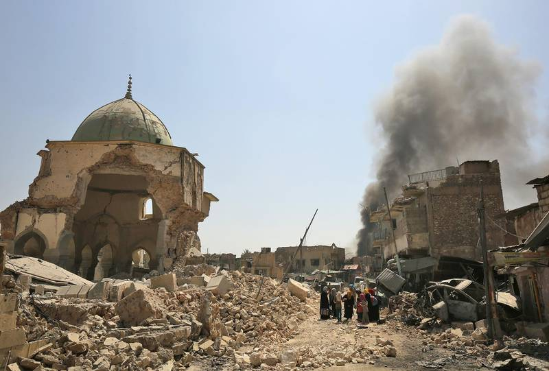 Displaced Iraqis walk past the destroyed Al-Nuri Mosque in the Old City of Mosul, as Iraqi government forces continue their offensive to retake the city from Islamic State (IS) group jihadists on June 30, 2017. - IS blew up the mosque and the famed Al-Hadba (hunchback) leaning minaret on June 21 as Iraqi forces closed in. (Photo by AHMAD AL-RUBAYE / AFP)