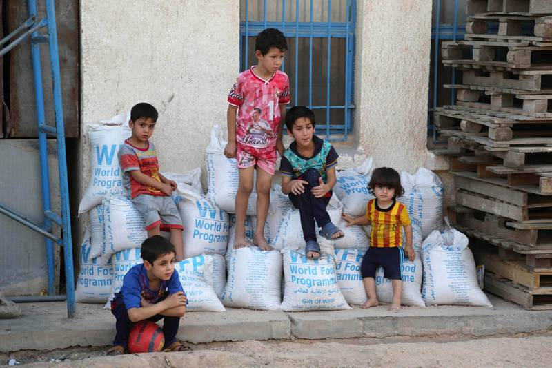 FILE - In this Friday, June 19, 2015 file photo, children sit on bags of rice from the World Food Program (WFP) at a school that serves as a shelter for internally displaced people in Baghdad's eastern district of Jamila, Iraq. The World Food Program on Friday, Oct. 9, 2020 won the 2020 Nobel Peace Prize for its efforts to combat hunger and food insecurity around the globe. (AP Photo/Karim Kadim, File)