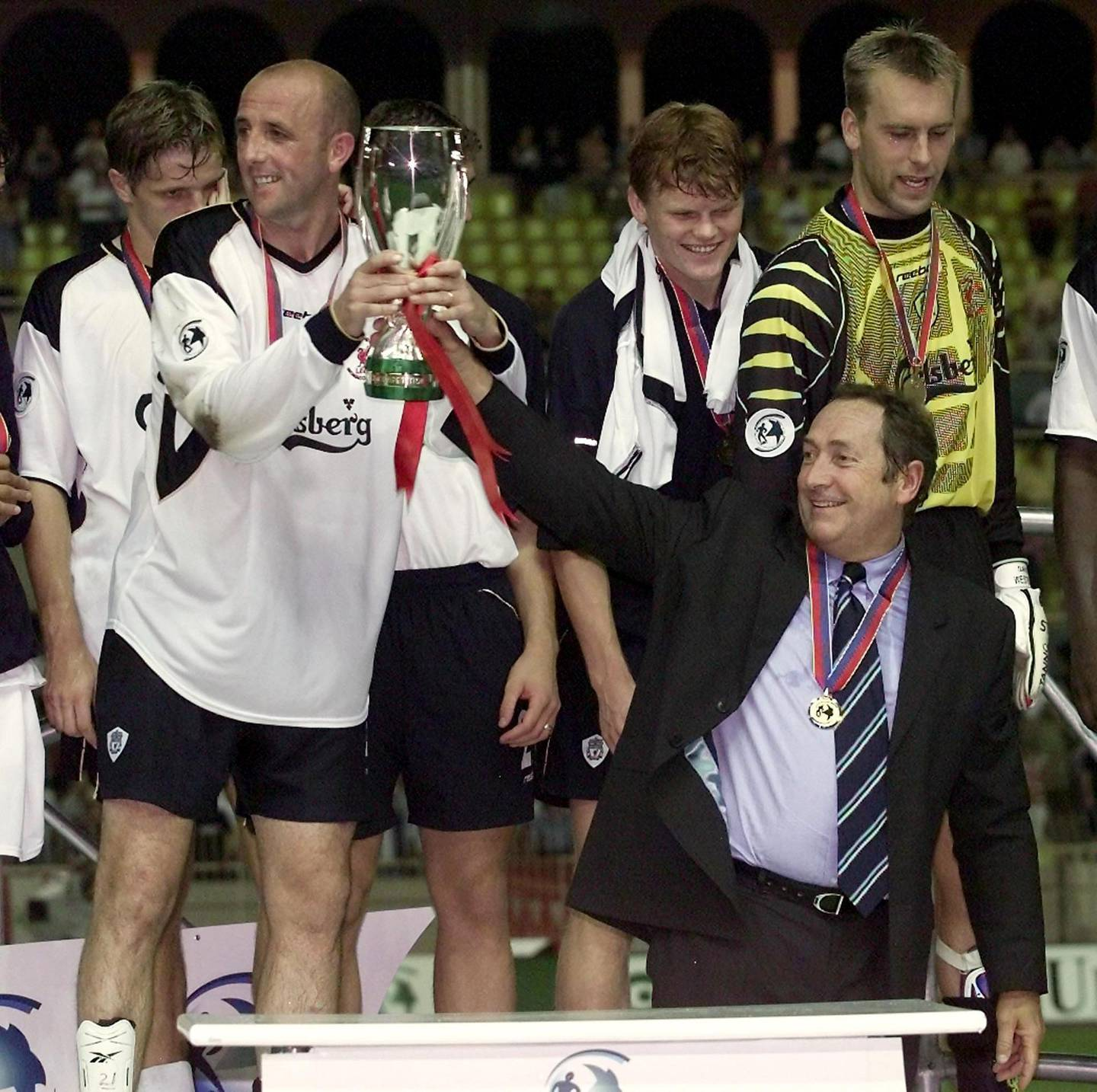 (FILES) In this file photo taken on August 24, 2001 Liverpool's French coach Gerard Houllier hoists the cup with team players after winning 3-2 against Bayern Munich in the European Super Cup held at Stade Louis II in Monaco. Ex-Liverpool manager Gerard Houllier has died at the age of 73, it was announced on December 14, 2020.  / AFP / JACQUES MUNCH