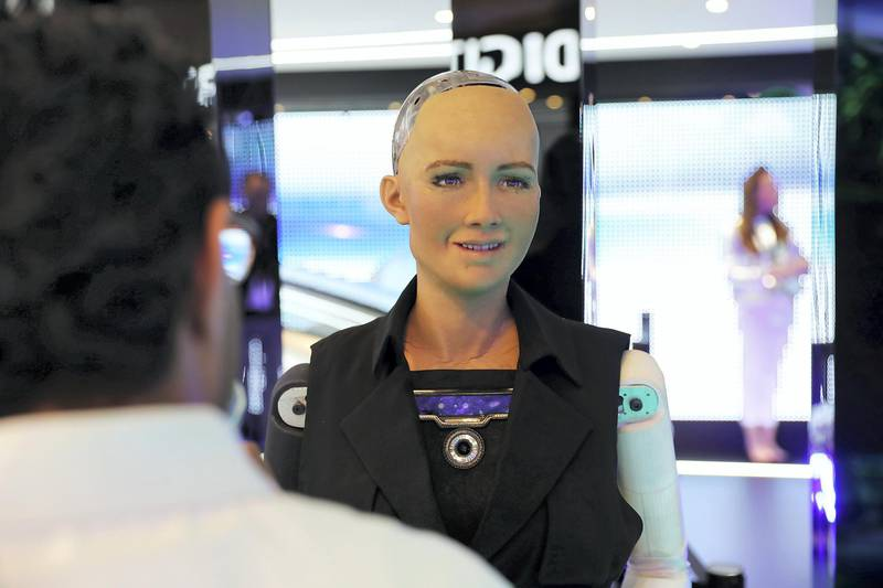 DUBAI , UNITED ARAB EMIRATES , OCT 10   – 2017 :- Visitors talking to social robot called 'Sophia' which is on display at the Etisalat stand during the GITEX Technology Week held at Dubai World Trade Centre in Dubai. (Pawan Singh / The National ) Story by Nicholas Webster