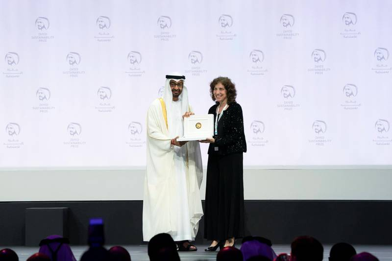ABU DHABI, UNITED ARAB EMIRATES - January 14, 2019:  HH Sheikh Mohamed bin Zayed Al Nahyan, Crown Prince of Abu Dhabi and Deputy Supreme Commander of the UAE Armed Forces (L), presents an award to a representative from 'We Care Solar', winners of the Zayed Sustainability Prize for Health, at Abu Dhabi National Exhibition Centre (ADNEC).   ( Hamed Al Mansoori / Ministry of Presidential Affairs ) ---