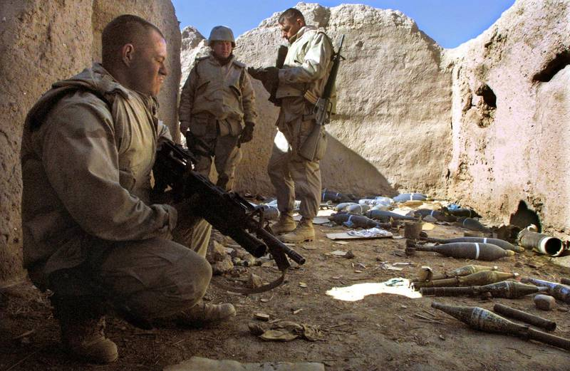 399708 04: U.S. Marine Sgt. Jerry Brown (L) of Jacksonville, North Carolina watches over a weapons cache found during a patrol near the American military compound at Kandahar Airport January 16, 2002 in Kandahar, Afghanistan. The Marines recovered mortars, rockets, rocket-propelled grenades and artillery rounds discovered in various caches near the base while on the patrol. (Photo by Mario Tama/Getty Images)