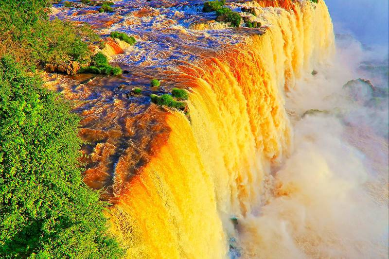 Impressive Iguacu falls at dramatic gold colored sunset, one of the most beautiful waterfalls in the world and one of the seven Wonders of Nature, dramatic beauty in nature landscape - Idyllic Devil's Throat - international border of Brazilian Foz do Iguacu city, Parana State, Argentina Puerto Iguazu city, Misiones province and Paraguay - rainforest landscape panorama, South America. Getty Images