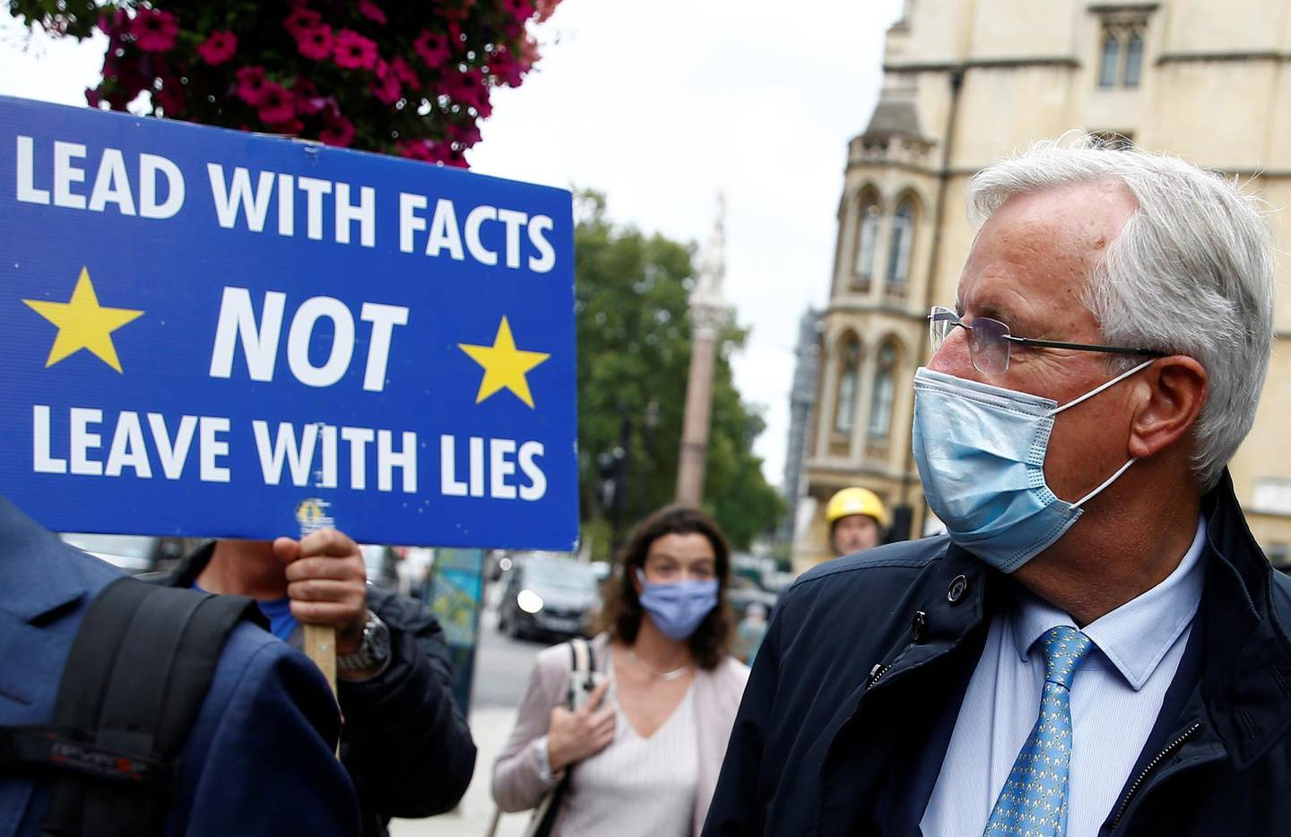 Anti-Brexit demonstrator Steve Bray holds a placard as EU's Chief Negotiator Michel Barnier walks with an entourage to a meeting in Westminster, London, Britain September 9, 2020. REUTERS/Henry Nicholls