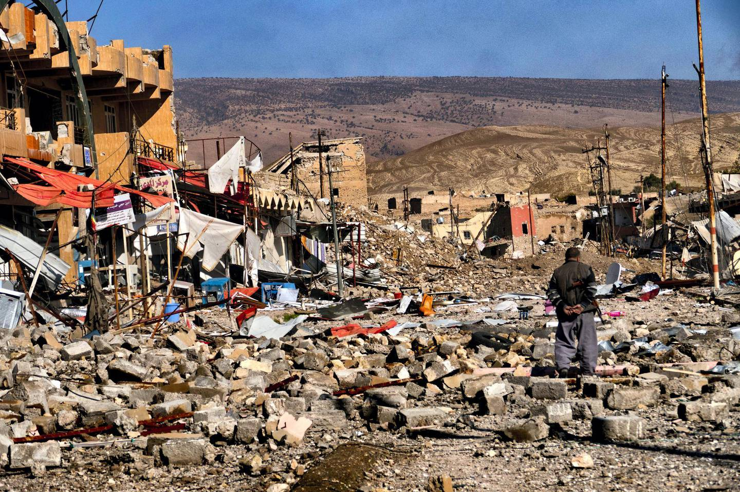 """SINJAR, REGIONAL GOVERNMENT OF KURDISTAN, IRAQ - 2015: A civilian walks among the ruins of the devastated town of Sinjar, after its liberation.  The town was liberated from ISIS on November 13th, 2015 by the Peshmerga forces of Iraqi Kurdistan. The Kurdish word """"Peshmerga"""" is used to refer to those who are part of Iraqi Kurdistan's armed forces. It means """"u201cone who confronts death,"""" or """"will fight to the death.""""u201d The capture of Sinjar by the Islamic State on August 3rd, 2014 was very violent. Over 35,000 Yazidi Kurd inhabitants attempted to flee into the nearby mountains. Those who could not escape were killed and the Yazidi women abducted by ISIS were sold or used as sex slaves. (Photo by Reza/Getty Images)"""