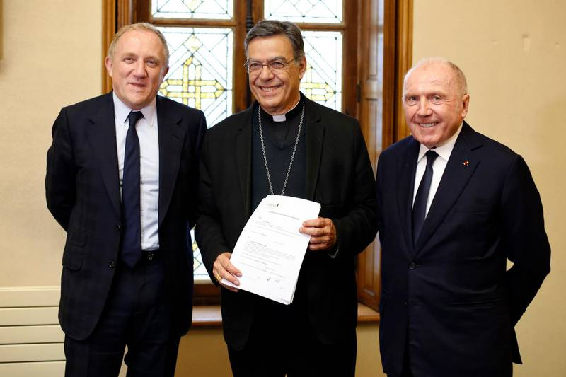 Francois-Henri Pinault, CEO of French luxury group Kering, left, his father Francois Pinault, right, and Archbishop of Paris Michel Aupetit, center, pose after signing an agreement to raise money for the rebuild of Notre-Dame cathedral, in Paris, Tuesday, Oct. 1, 2019. French billionaire Francois Pinault and his son Francois-Henri Pinault have made a 100 million euros ($109 million) donation for the rebuilding of Notre Dame Cathedral. (AP Photo/Thibault Camus)