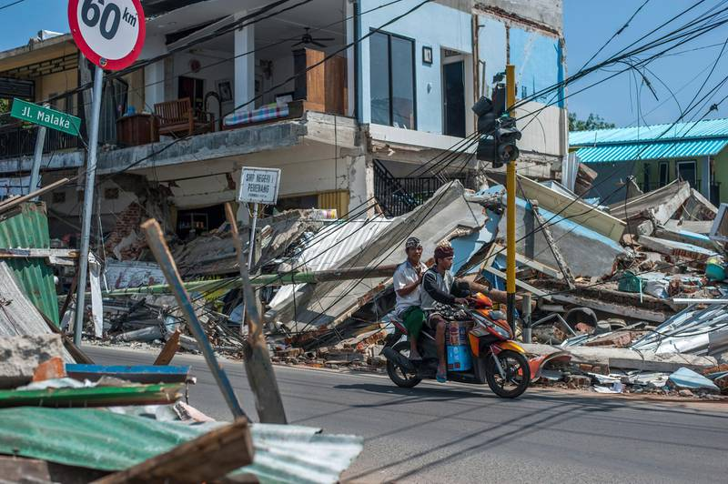 In this Friday, Aug. 10, 2018, photo, motorists ride past buildings ruined by Sunday's earthquake in Pamenang, Lombok Island, Indonesia. The north of the popular resort island has been devastated by Sunday's earthquake, damaging thousands of buildings and killing a large number of people. (AP Photo/Fauzy Chaniago, File)