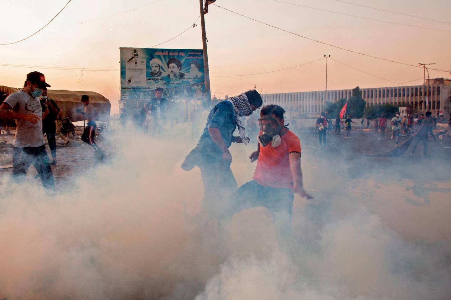 TOPSHOT - Iraqi protesters wear masks to protect themselves from tear gas as they take part in an anti-goverment demonstration in the southern city of Basra on November 8, 2019.  Anti-government protests in Iraq entered their third week today amid fresh bloodshed. In Basra, seven protesters were killed in confrontations yesterday and early today, with security forces trying to reopen roads blocked by sit-ins, medical sources said. / AFP / Hussein FALEH