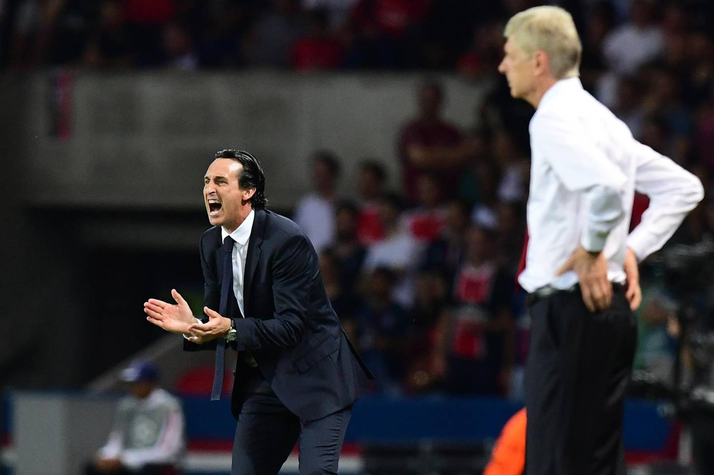 """(FILES) In this file photo taken on September 13, 2016, Paris Saint-Germain's Spanish head coach Unai Emery (L) gestures next to Arsenal's French manager Arsene Wenger during the UEFA Champions League Group A football match between Paris-Saint-Germain vs Arsenal FC, at the Parc des Princes stadium in Paris. Unai Emery has been appointed as the new manager of Arsenal, the club announced on May 23, 2018. """"Unai Emery is to become our new head coach,"""" said a statement on the club's website. """"He joins the club after completing a two-year spell at Paris Saint-Germain, where he recently landed the treble of Ligue 1, Coupe de France and the Coupe de la Ligue."""" / AFP / FRANCK FIFE AND FRANCK FIFE"""