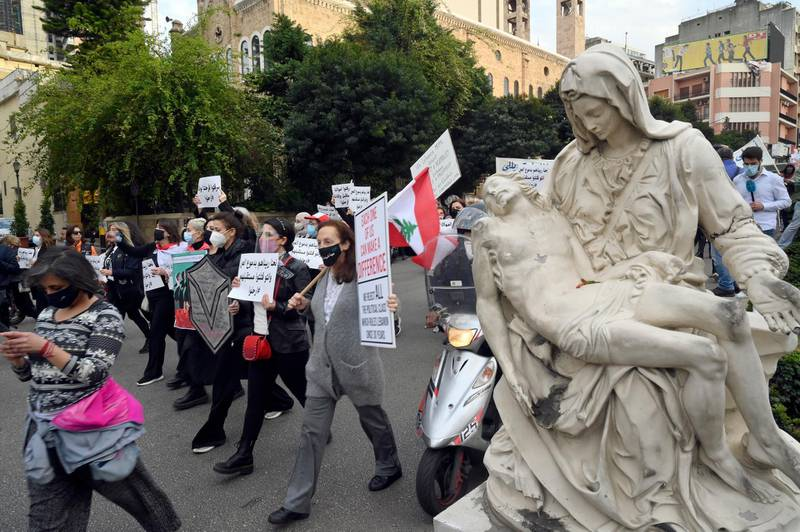 epa09086257 Lebanese women carry placards as they march on the occasion of Mother's Day under the slogan 'Mother's Cry', in Beirut, Lebanon, 20 March 2021. Mother's Day is celebrated in various countries on 21 March.  EPA/WAEL HAMZEH