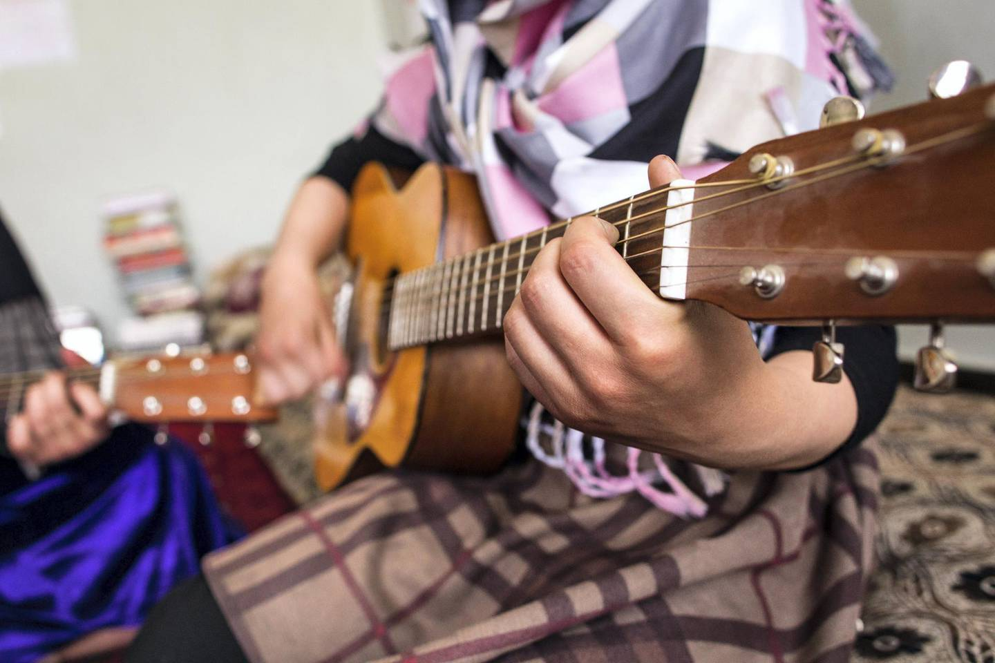 May 12, 2017 - Kabul, Kabul, Afghanistan: Two girls practice chord progressions on guitars. The children study with Lanny Cordola in Kabul.Cordola's work has grown increasingly challenging as the security situation in Kabul has worsened.(Ivan Flores/The National)