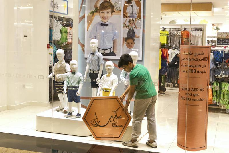 DUBAI, UNITED ARAB EMIRATES - JUNE 13, 2018. A young boy adjusts a Eid Mubarak sign at Mall of the Emirates on the 28th day of Ramadan.(Photo by Reem Mohammed/The National)Reporter: Section: NA
