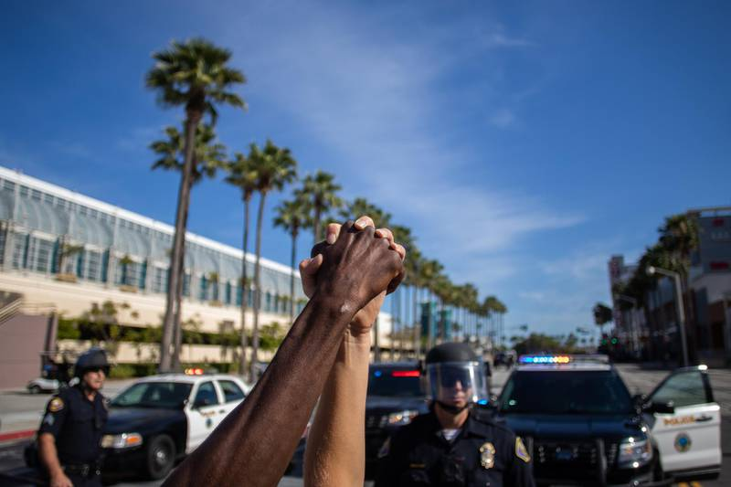 A black man and a white woman hold their hands up in a front of police officers in downtown Long Beach on May 31, 2020 during a protest against the death of George Floyd, an unarmed black man who died while being arrested and pinned to the ground by the knee of a Minneapolis police officer. - Protests sweeping the United States over the death of George Floyd reverberated on the other side of the globe Monday when thousands marched in solidarity on the streets of New Zealand. (Photo by Apu GOMES / AFP)