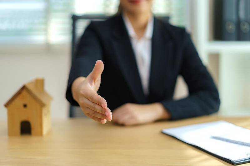 Real estate broker businesswoman ready to shakehand to seal a deal with her customer signing a contract: real estate, home loan and insurance concept. Getty Images