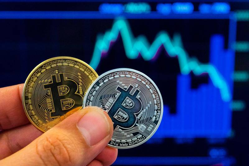 """(FILES) In this file photo taken on February 06, 2018 A picture taken on February 6, 2018 shows a person holding a visual representation of the digital crypto-currency Bitcoin, at the """"Bitcoin Change"""" shop in the Israeli city of Tel Aviv. Bitcoin miners, whose computer processors enable the running of the world's most popular virtual currency, will soon face a quadrennial event that alters the profitability of the hi-tech industry. So-called """"halving"""" is when bitcoin-mining companies and individuals discover what they will receive in return for their contribution to the system's smooth operation.  / AFP / JACK GUEZ / TO GO WITH STORY BY KEVIN TRUBLET"""