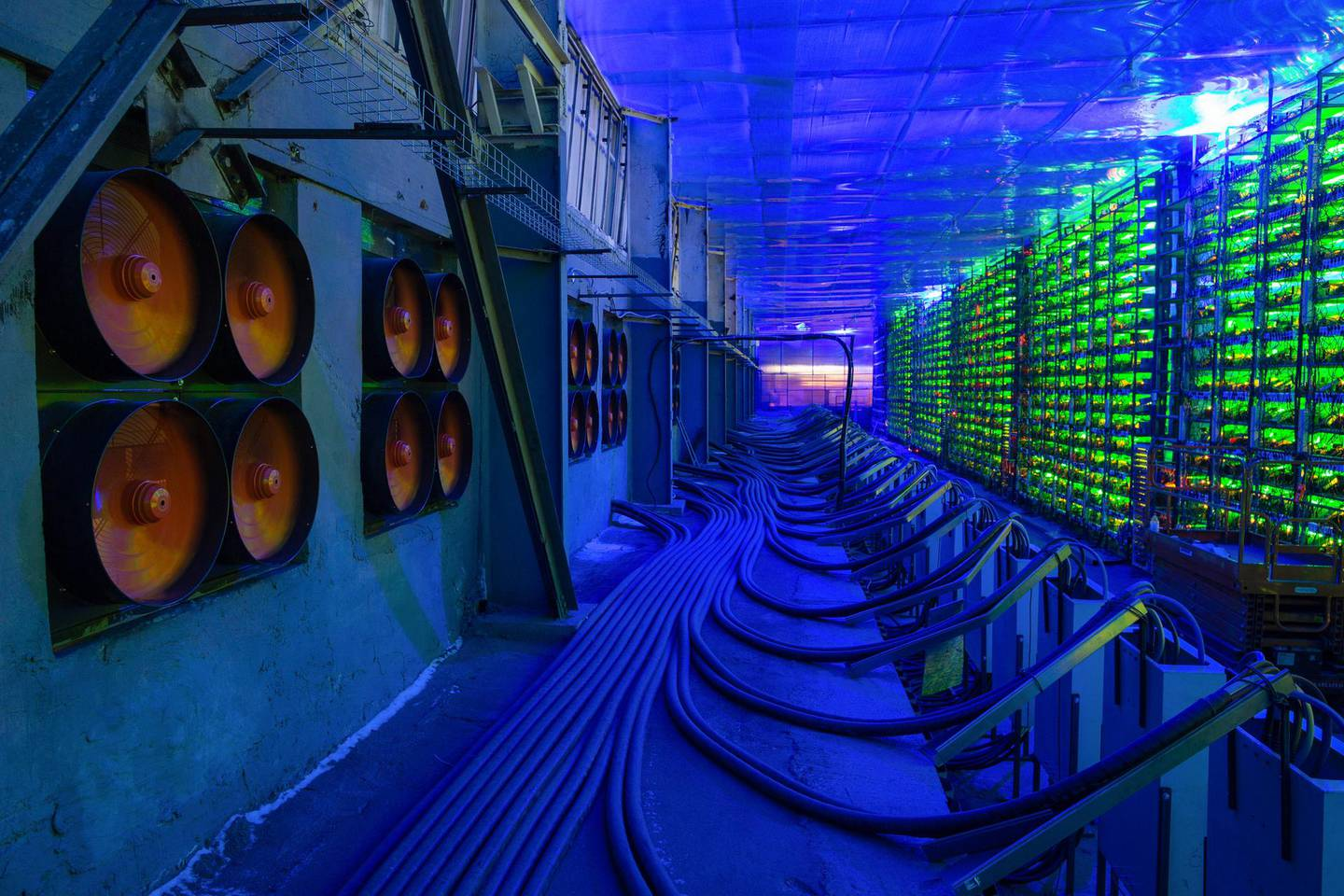 Industrial cooling fans operate to thermally regulate illuminated mining rigs at the CryptoUniverse cryptocurrency mining farm in Nadvoitsy, Russia, on Thursday, March 18, 2021. The rise of Bitcoin and other cryptocurrencies has prompted the greatest push yet among central banks to develop theirown digital currencies. Photographer: Andrey Rudakov/Bloomberg