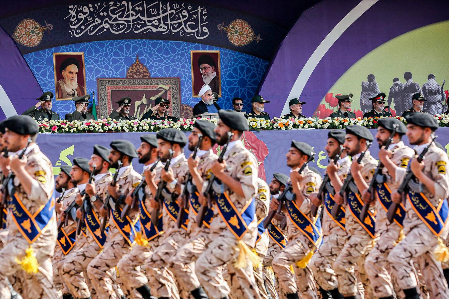 """A handout picture provided by the Iranian presidency on September 22, 2019 shows President Hassan Rouhani (C) and other top military commanders watching members the Islamic Revolutionary Guard Corps (IRGC) marching past during the annual """"Sacred Defence Week"""" military parade marking the anniversary of the outbreak of the devastating 1980-1988 war with Saddam Hussein's Iraq, in the capital Tehran. - Rouhani said on September 22 that the presence of foreign forces creates """"insecurity"""" in the Gulf, after the US ordered the deployment of more troops to the region. """"Foreign forces can cause problems and insecurity for our people and for our region,"""" Rouhani said in a televised speech at the annual military parade, adding that Iran would present to the UN a regional cooperation plan for peace. (Photo by - / Iranian Presidency / AFP) / === RESTRICTED TO EDITORIAL USE - MANDATORY CREDIT """"AFP PHOTO / HO / IRANIAN PRESIDENCY"""" - NO MARKETING NO ADVERTISING CAMPAIGNS - DISTRIBUTED AS A SERVICE TO CLIENTS ==="""