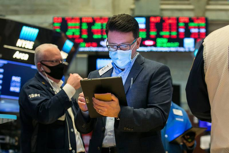 In this photo provided by the New York Stock Exchange, trader Americo Brunetti, center, works on the floor, Tuesday, Feb. 9, 2021. Stocks were slightly lower in early trading on Tuesday, after the major stock market indexes hit record highs the day before. Investors continue to keep their eyes on Washington, where it appears Democrats plan to move ahead without Republican help on a major stimulus bill for the economy. (Courtney Crow/New York Stock Exchange via AP)