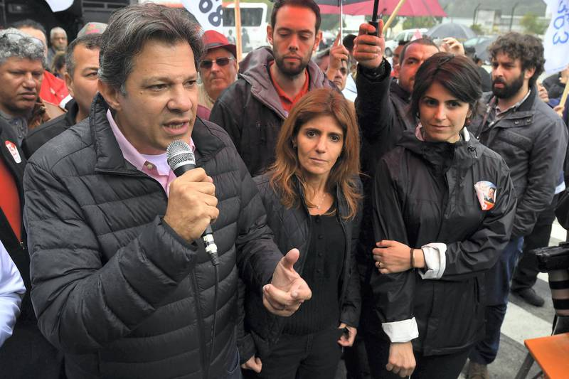 Brazilian vice-presidential candidate for the Worker's Party (PT) Fernando Haddad (L), speaks at the entrance of the Volkswagen plant next to Manuela D'Avila (R), of Brazil's Communist Party (PCdoB), in Sao Bernardo do Campo, some 25 km from Sao Paulo, Brazil, on September 5, 2018, ahead of the October 7 national election. Leftist ex-president Luiz Inacio Lula da Silva will appeal his barring from October's elections to the United Nations and Brazil's Supreme Court, Haddad -the man set to replace him on the ballot- said eralier this week. / AFP PHOTO / NELSON ALMEIDA