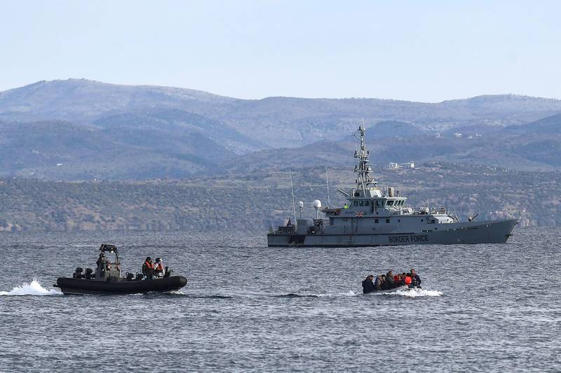 A dinghy with 15 Afghan refugees, 5 children, 3 women and 7 men, approaches the Greek island of Lesbos on February 28, 2020 next to UK Border Force patrol boat HMC Valiant (background), a cutter patroling in Agean sea under European Union border force Frontex. - Turkey will no longer close its border gates to refugees who want to go to Europe, a senior official told AFP on February 28, shortly after the killing of 33 Turkish soldiers in an airstrike in northern Syria. (Photo by ARIS MESSINIS / AFP)