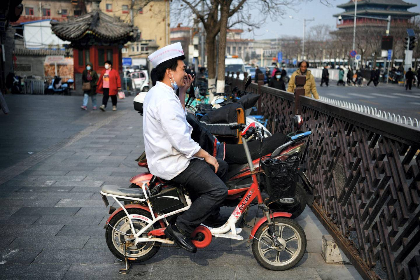 A chef sitting on an electric bike makes a phone call in Beijing on March 8, 2021. (Photo by GREG BAKER / AFP)