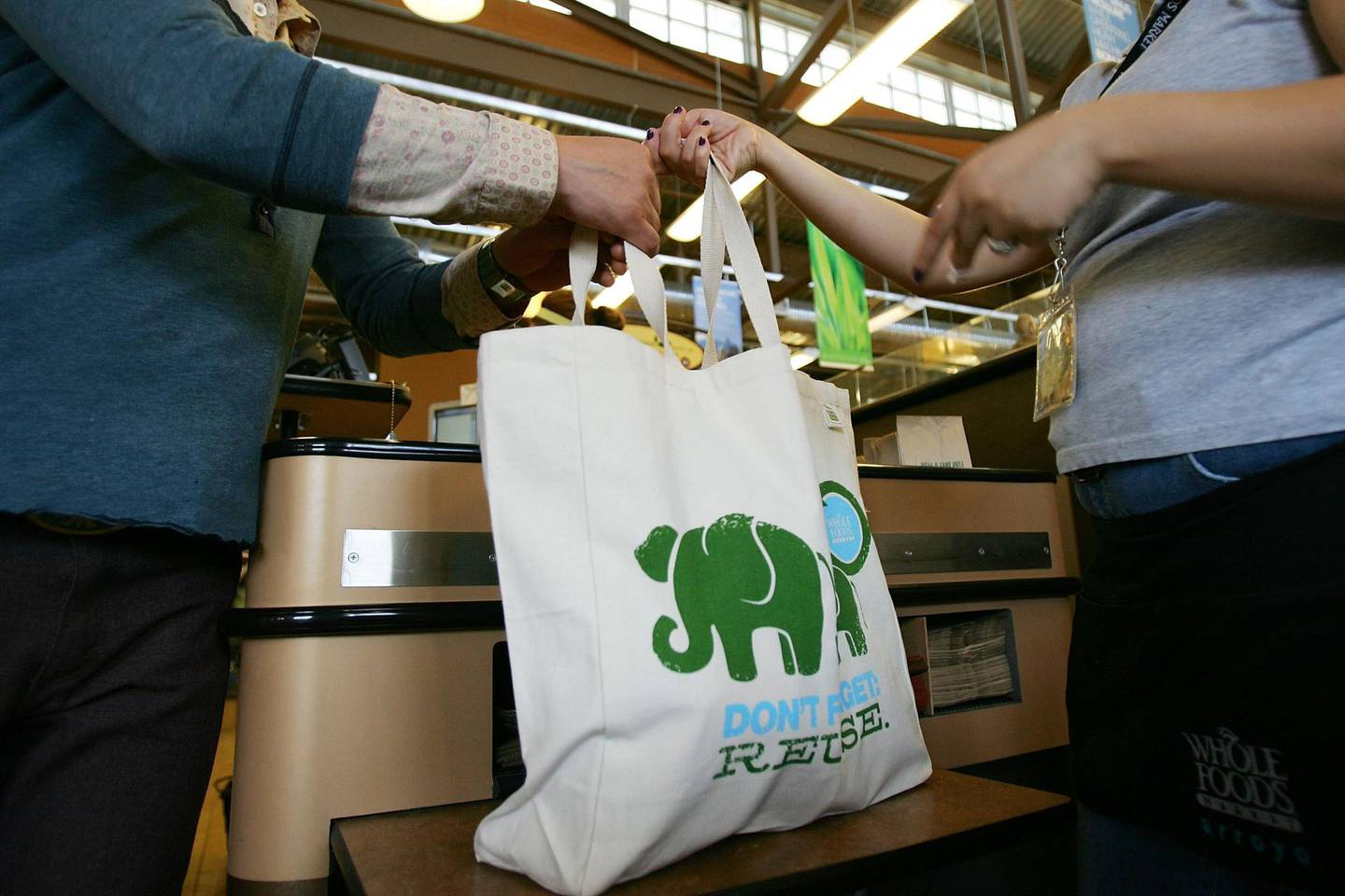 PASADENA, CA - APRIL 22:  Employees hand out free reusable grocery bags at a Whole Foods Market natural and organic foods stores which is ending the use of disposable plastic grocery bags in its 270 stores in the US Canada and UK on Earth Day, April 22, 2008 in Pasadena California. The use of reusable bags has increased since a statewide plastic bag recycling law was enacted in July 2007 requiring grocers to provide in-store plastic bag recycling and to sell reusable shopping bags. Some communities have banned disposable single-use plastic shopping bags because they don't break down in landfills, and clog waterways, endangering wildlife, and are a major source of litter.   (Photo by David McNew/Getty Images)